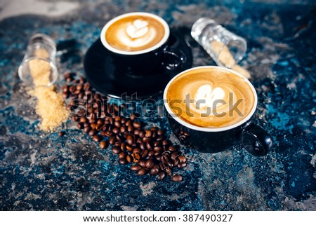 two cups of coffee with latte art. Barista pouring coffee - stock photo