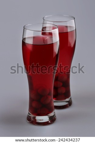 Two cups of compote of cherries on a gray background - stock photo