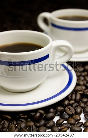 Two cups of espresso coffee on a coffee bean surface. - stock photo