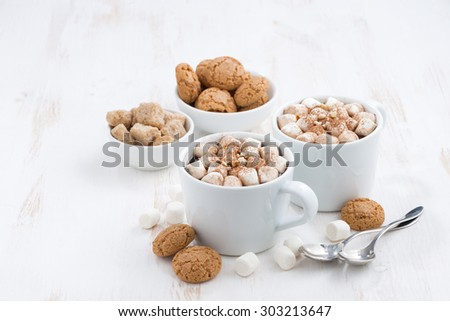 two cups of flavored cocoa with marshmallow and cookies on white background, top view - stock photo