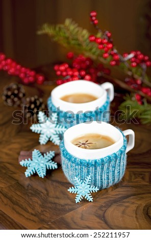 Two cups of freshly brewed espresso coffee , sweet snowflakes, almond cookies on a textured wooden table - stock photo