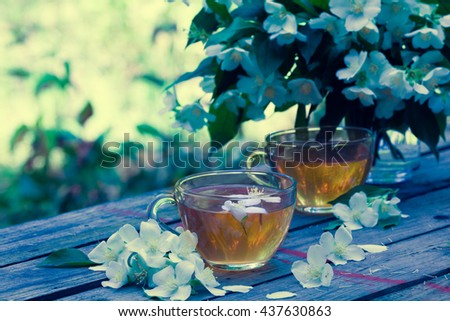 Two cups of green tea with jasmine flowers on grunge wooden table outdoors. Blue vintage color - stock photo
