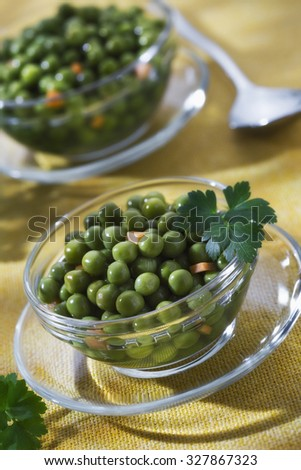 Two cups of peas on yellow table with parsley - stock photo