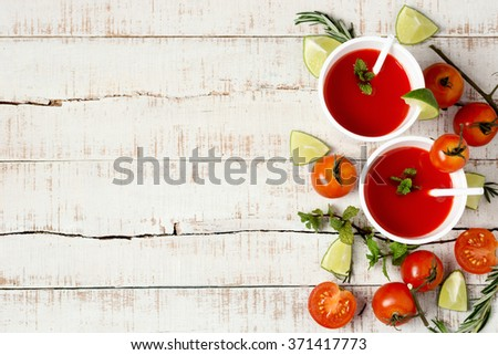 two cups of red healthy drink among tomatoes, limes, rosemary and mint sprigs. detox background - stock photo