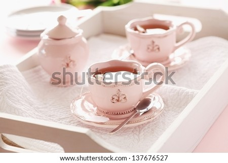 Two cups of tea with a teapot and spoon on a wooden tray. - stock photo
