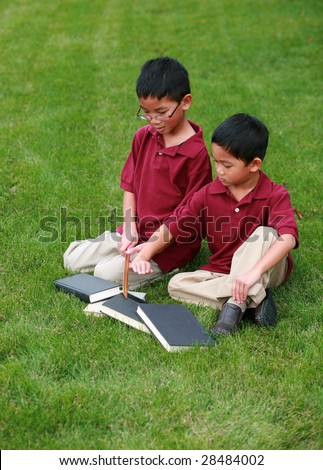 two cute asian boys reading in grass - stock photo