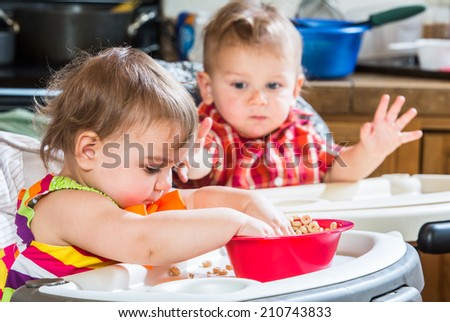 Two cute babies are eating breakfast together - stock photo