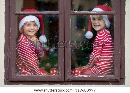 Two cute boys, brothers, looking through a window, drinking tea and waiting impatiently for Santa. Christmas concept - stock photo
