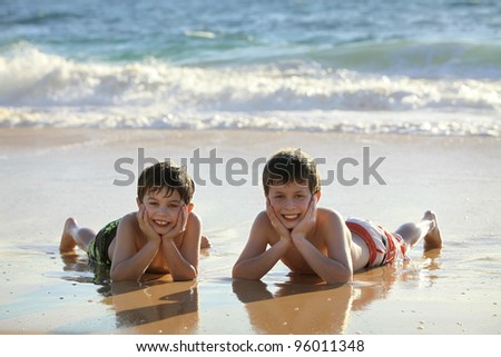 two cute boys laying at the beach - stock photo
