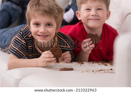 two cute boys lying on couch. two friends eating cookies and smiling - stock photo