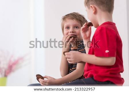 two cute boys sitting on couch. two friends eating cookies and talking - stock photo