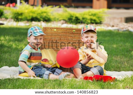 Two cute boys sitting on ground - stock photo