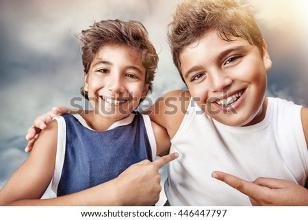 Two cute cheerful boys hugging and showing on each other by finger, portrait over cloudy sky background, happy children having fun at summertime - stock photo