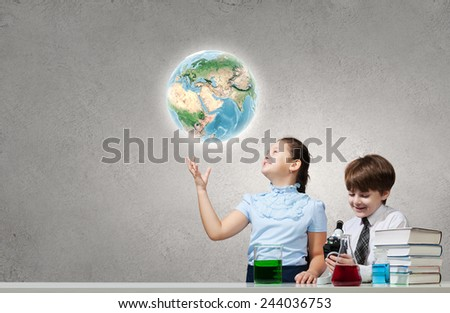 Two cute children at chemistry lesson making experiments. Elements of this image are furnished by NASA - stock photo