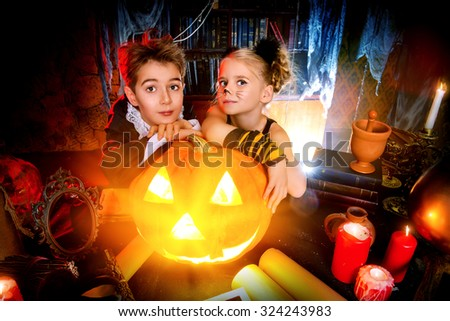 Two cute children dressed as a vampire and a black cat posing with pumpkin in a halloween room. Halloween concept. - stock photo