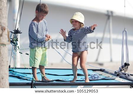 two cute children in sailor t-shirt on sea catamaran / yacht - stock photo