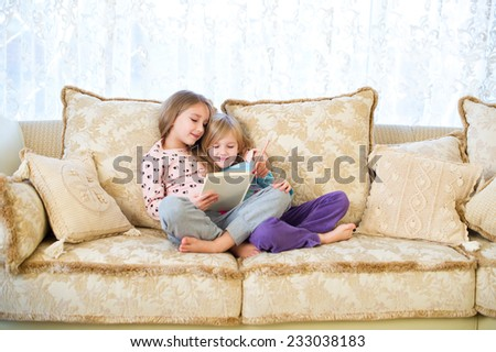 Two cute european sister girls reading a book for children and having fun in room of their home - stock photo