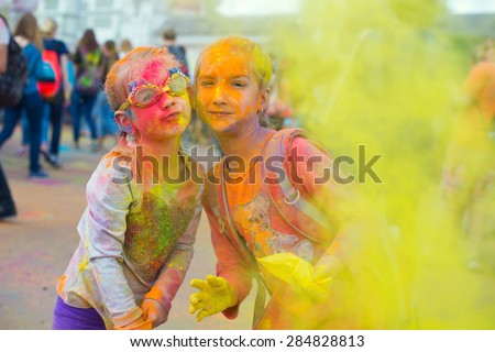 Two cute european sisters child girls celebrate Indian holi festival with colorful paint powder on faces and body - stock photo