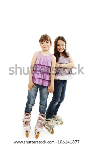 Two cute girls holding hands wearing roller skates. Isolated on a white background - stock photo