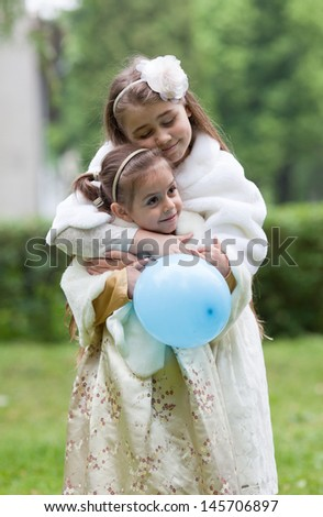 Two cute girls in ornate dress, aged 5 and 10, hugging and smiling. Outdoors - stock photo