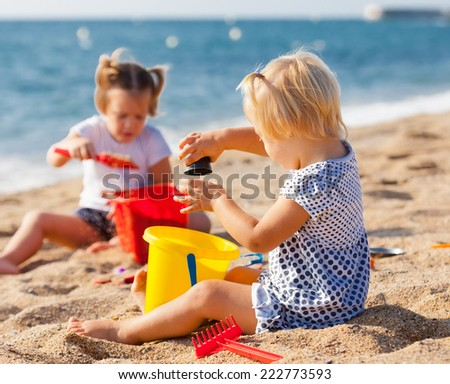 Two cute girls playing on the beach - stock photo