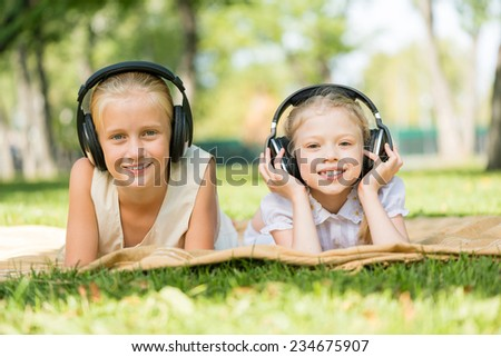 Two cute girls wearing headphones lying in park - stock photo