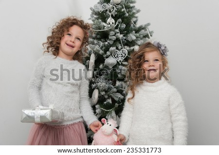 Two cute girls with sheep toy and gifts near Christmas tree on white background - stock photo