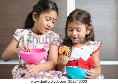 Two cute Indian girls eating traditional snack murukku. Asian sibling or children enjoying food, living lifestyle at home. - stock photo