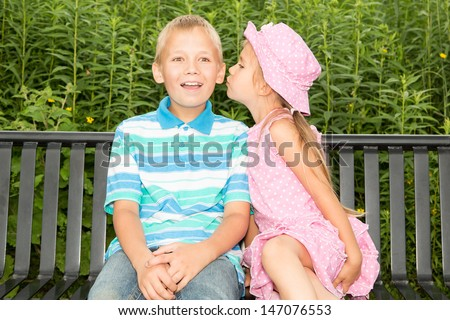Two cute kids sitting on a park bench, the girl is trying to whisper something to the boy's ear, or maybe even to kiss him in the cheek ! - stock photo
