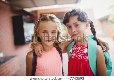 Two cute kids with arms around each other during the first day of school - stock photo