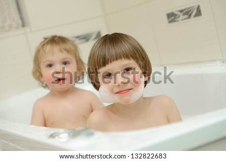 Two cute little boys having a bath together - stock photo