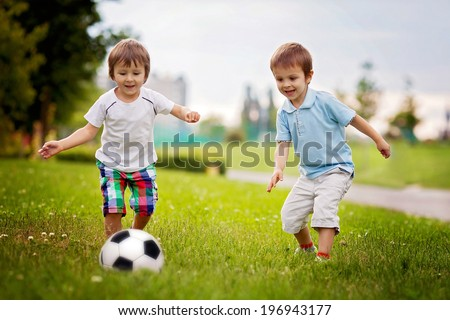 Two cute little boys, playing football - stock photo