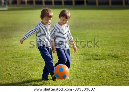 Two cute little boys, playing football outdoor, autumn time - stock photo