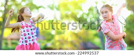 Two Cute little girl playing badminton  - stock photo