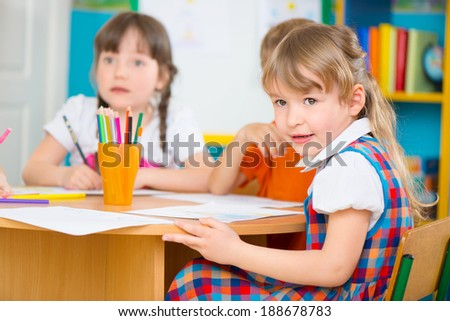 Two cute little girls drawing at kindergarten - stock photo