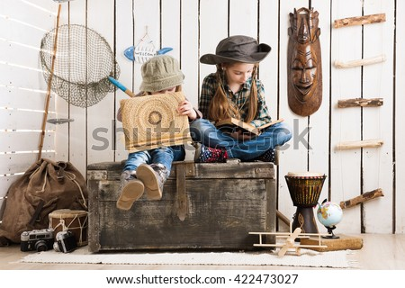 two cute little girls in cowboy hats sitting on wooden chest and watching album - stock photo