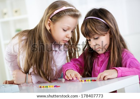 Two cute little girls playing at home. - stock photo