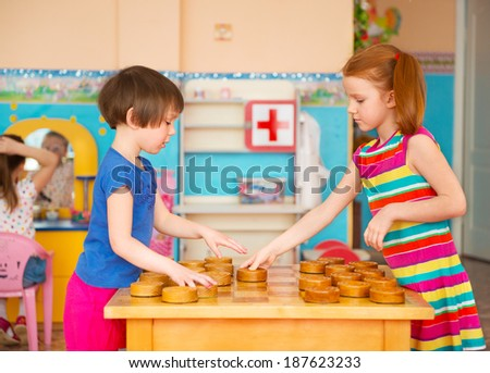 Two cute little girls playing in checkers at kindergarten - stock photo