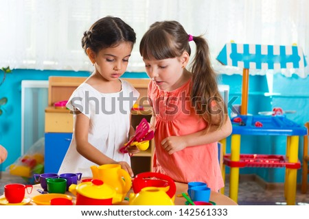 Two cute little girls playing role game in daycare - stock photo