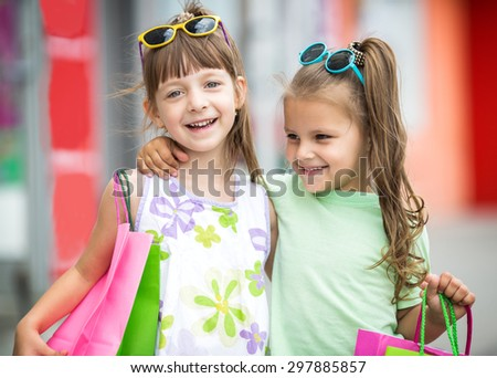 two cute little girls with shopping bags in city - stock photo