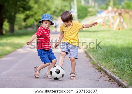 Two cute little kids, playing football together, summertime. Children playing soccer outdoor - stock photo