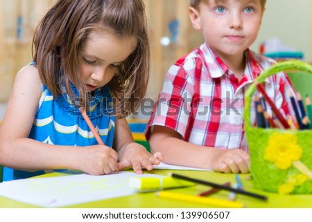 Two cute little prescool kids drawing with crayons at the table - stock photo
