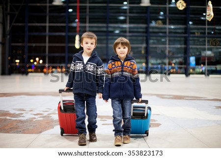 Two cute little sibling children, boys, at the airport, traveling together on Christmas - stock photo
