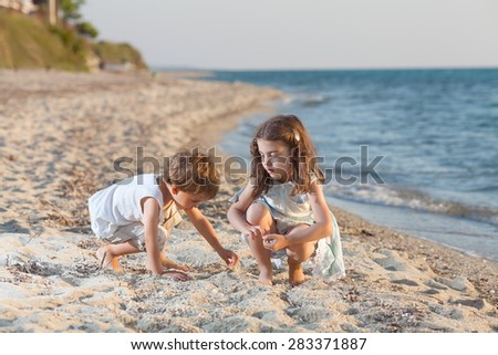 Two cute little siblings playing on the beach - stock photo