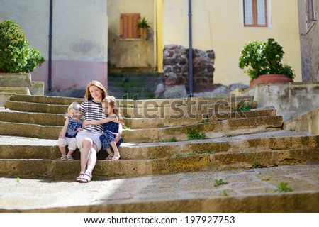 Two cute little sisters and their mother  sitting on stairs in italian town - stock photo