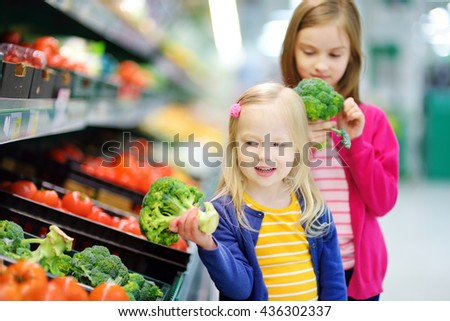Two cute little sisters choosing fresh broccoli in a food store or a supermarket - stock photo