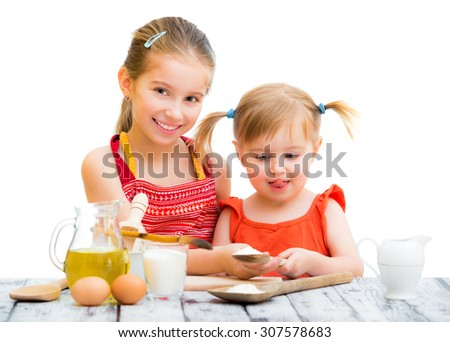 two cute little sisters cooking, white background - stock photo