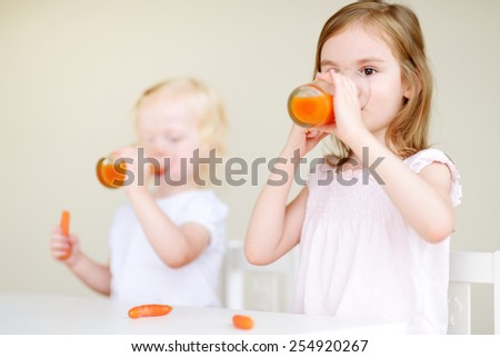 Two cute little sisters eating carrots and drinking carrot juice - stock photo