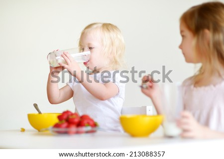 Two cute little sisters eating cereal with strawberries and drinking milk in white kitchen - stock photo