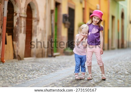 Two cute little sisters having fun outdoors on beautiful sunny day in italian town - stock photo
